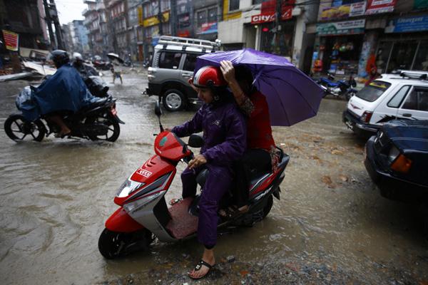 A girl negotiating a waterlogged road with the pillion rider carrying an umbrella in Baneshwor,  Kathmandu, on Wednesday. PHOTO/SKANDA GAUTAM/THT/AFP