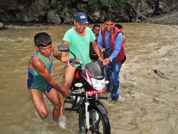 Locals taking a bike across the swollen Ratikhola, in Dailekh, on Friday. Photo:THT