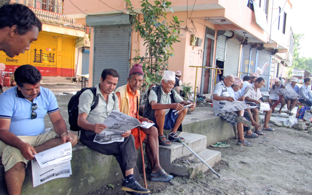 People reading newspapers in Chautara, Khairenitar of Tanahun, on Saturday. Photo: THT
