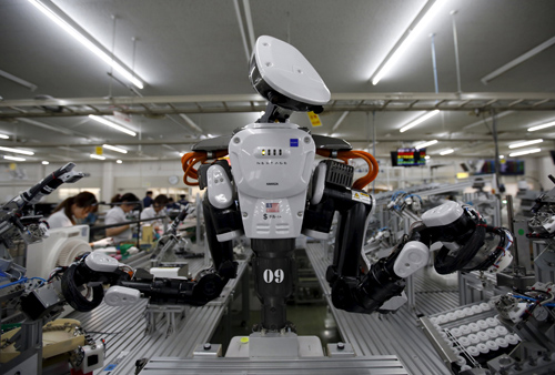 A humanoid robot works side by side with employees in the assembly line at a factory of Glory Ltd., a manufacturer of automatic change dispensers, in Kazo, north of Tokyo, Japan, in this July 1, 2015 file photo. Glory is in the vanguard as Japanese firms ramp up spending on robotics and automation, responding at last to premier Shinzo Abe's efforts to stimulate the economy and end two decades of stagnation and deflation. Photo: Reuters