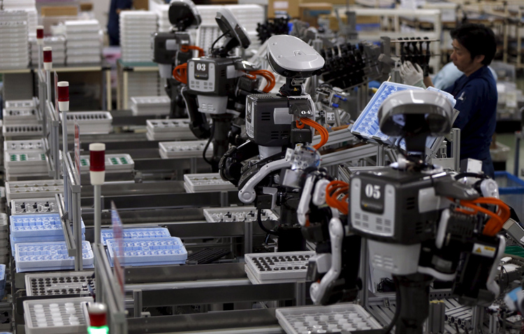 Humanoid robots work side by side with employees in the assembly line at a factory of Glory Ltd., a manufacturer of automatic change dispensers, in Kazo, north of Tokyo, Japan, in this July 1, 2015 file photo. Glory is in the vanguard as Japanese firms ramp up spending on robotics and automation, responding at last to premier Shinzo Abe's efforts to stimulate the economy and end two decades of stagnation and deflation. Photo: Reuters