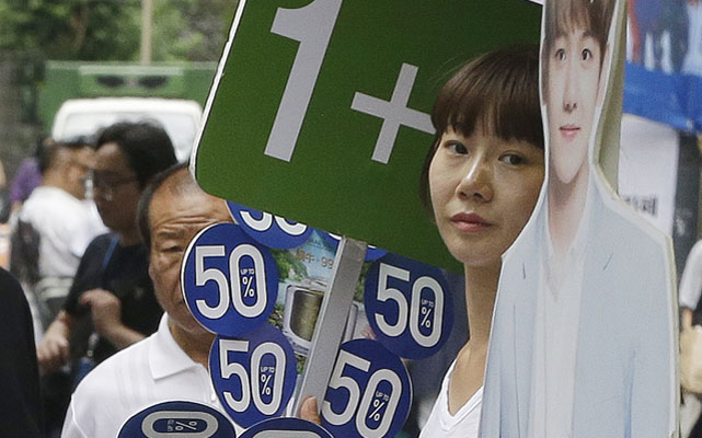 A sales clerk holding discount sale signs as she waits for customers in Seoul. South Korea's central bank cut its economic growth forecast on Thursday, citing a severe drought and the spread of MERS. Photo: AP