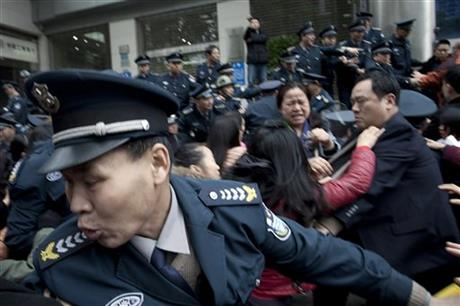 In this March 19, 2015 photo, security guards scuffle with protestors angry about failed investments with Hunan Bofeng Asset Management Ltd. outside of a branch of the Industrial and Commercial Bank of China in Changsha in southern China's Hunan province. AP