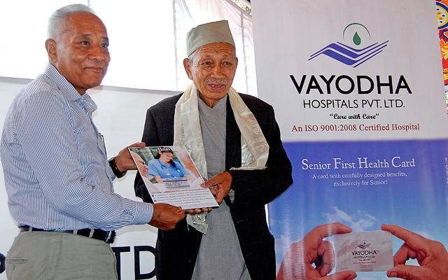 Dr Manoharlal Shrestha of Vayodaha Hospital handing over the senior citizen health card to historian Satyamohan Joshi, in Balkhu, Kathmandu on Satuday. Photo: THT