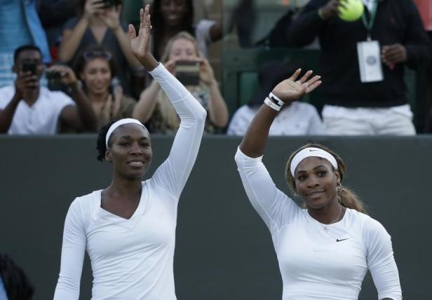 Venus Williams of the U.S. (L) and Serena Williams of the U.S.wave after defeating Oksana Kalashnikova of Georgia and Olga Savchuk of Ukraine in their women's doubles tennis match at the Wimbledon Tennis Championships, in London June 25, 2014.      Photo: Reuters