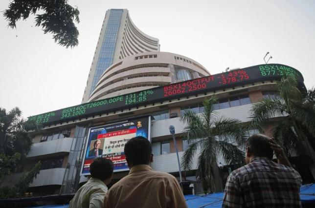 People watch a large screen displaying India's benchmark share index on the facade of the Bombay Stock Exchange (BSE) building in Mumbai October 16, 2014. REUTERS/Shailesh Andrade