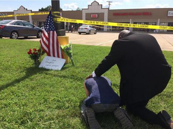 A man prays over a sobbing citizen next to a US flag at the site of a shooting attack on a Naval recruiting center in Chattanooga, Tennesse July 16, 2015. Photo: Reuters