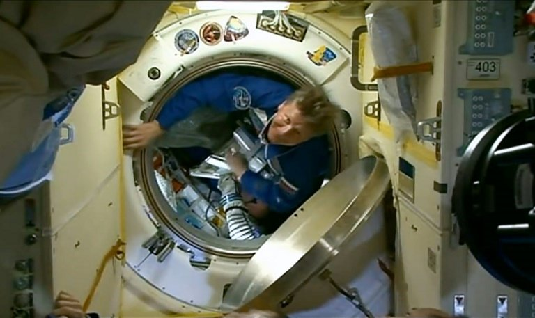 This March 28, 2015 still image from NASA TV shows Russian cosmonaut Gennady Padalka entering the International Space Station. Photo: AFP