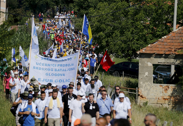 People marching near the village of Nezuk, in Bosnia and Herzegovina, on Wednesday. Several thousand people started  a march from Nezuk to  Srebrenica to retrace the route in reverse taken by Bosnian Muslims fleeing Serb forces in 1995.nPhoto: Reuters