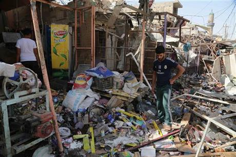 Civilians gather at the scene of a suicide car bombing at a busy market in Khan Bani Saad in the Diyala province, about 20 miles (30 kilometers) northeast of Baghdad, Iraq, Saturday, July 18, 2015. AP