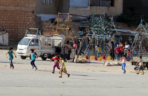 Children run as they flee from a makeshift playground after hearing the sound of a Syrian fighter jet hovering over Idlib city, Syria July 18, 2015. Photo: nREUTERS/AMMAR ABDULLAH