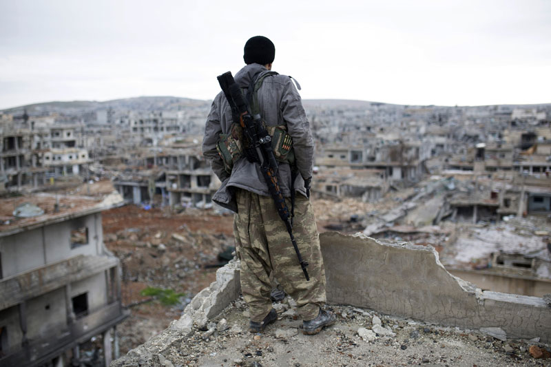 In this Jan. 30, 2015, file photo, a Syrian Kurdish sniper looks at the rubble in the Syrian city of Ain al-Arab, also known as Kobani. Turkeyu2019s dramatic air campaign against the Islamic State and Kurdish forces has created a bit of a conundrum for President Barack Obama, who is leading the fight against one of Turkeyu2019s targets while relying heavily on the other target. Photo: AP