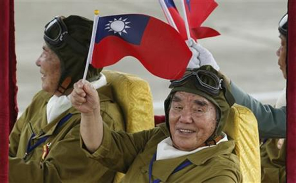 Taiwan's WWII military veterans wave to spectators during a massive parade marking the 70th anniversary of the end of WWII, at the military base in Hsinchu, northern Taiwan, Saturday, July 4, 2015. Taiwan marched out thousands of troops and displayed its most modern military hardware Saturday to spotlight an old but often forgotten claim that its forces, not the Chinese Communists, led the campaign that routed imperial Japan from China 70 years ago. Photo: AP