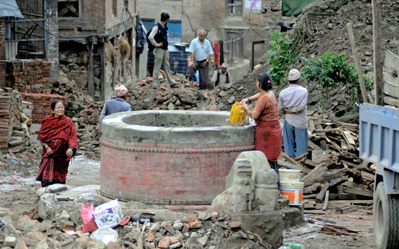 A woman taking out water from a well as locals look at the debris of houses that were destroyed by the quakes, in Bhaktapur, on Wednesday. Photo: THT