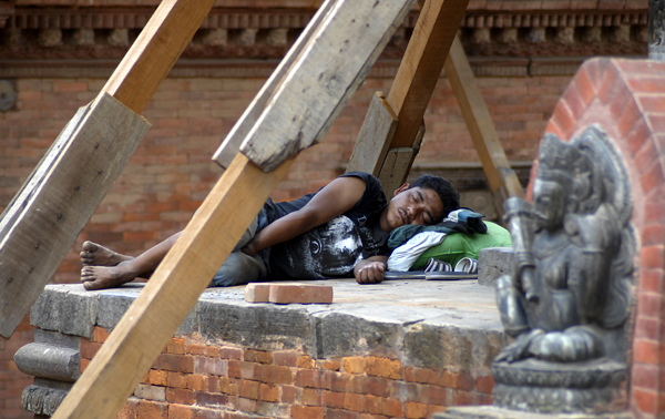 A man taking a nap under a vulnerable temple, supported by wooden beams, which is declared a prohibited zone, in Lalitpur, on Wednesday. nPhoto: THT