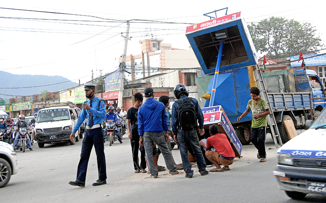 Workers removing an old structure for traffic cops to stand while managing traffic to replace that with a new one, in Lainchaur, on Thursday. Photo: THT