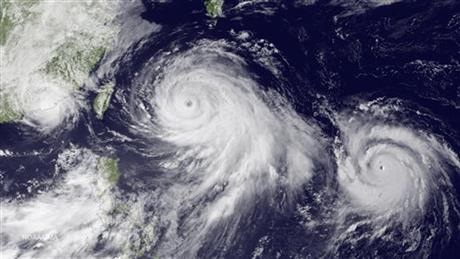 This satellite image taken by the JMA MTSAT-2 satellite at 9;30 a.m. EDT on Thursday, July 9, 2015, shows Tropical Storm Linfa, left, tracking westward parallel to the coast of China, and Typhoon Chan-hom, over the Ryukyu Trench south of Okinawa, Japan, on a track heading northwest toward the China coast north of Wenzhou. Southeastern provinces in China were alerted about possible flooding and severe weather this week from both approaching storms. Photo: AP