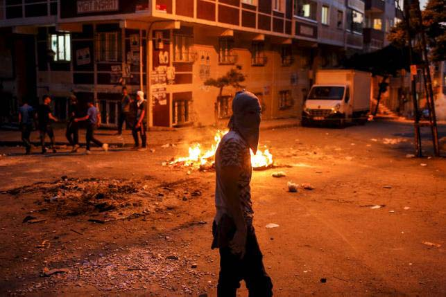 A far left-wing protester walks past a burning barricade during clashes with riot police at a demonstration against the death of Gunay Ozarslan, a member of the far left People's Front who, according to local media reports, was killed by Turkish police during a security operation on Friday, in Istanbul's Gazi neighborhood, Turkey, July 26, 2015. Photo: Reuters