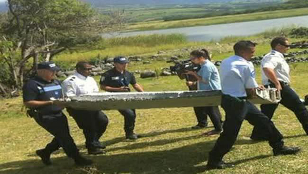 Police carrying a piece of debris from an unidentified aircraft found in the coastal area of Saint-Andre, east of the Indian Ocean island of La Reunion, on Wednesday.  Photo:AFP