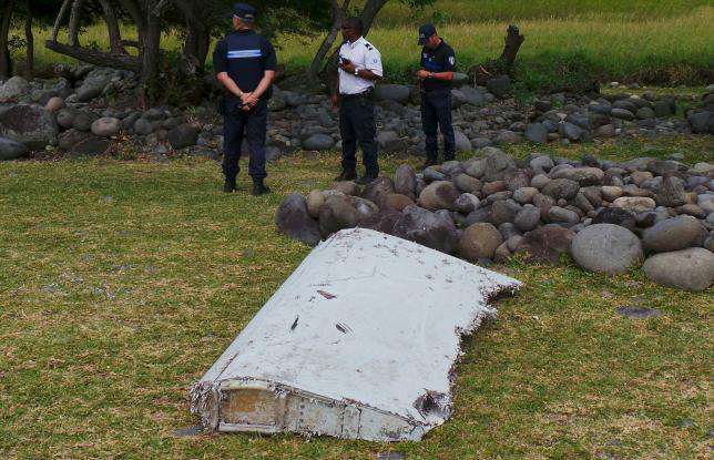 French gendarmes and police stand near a large piece of plane debris which was found on the beach in Saint-Andre, on the French Indian Ocean island of La Reunion, July 29, 2015. Photo: REUTERS/ZINFOS974/PRISCA BIGOT