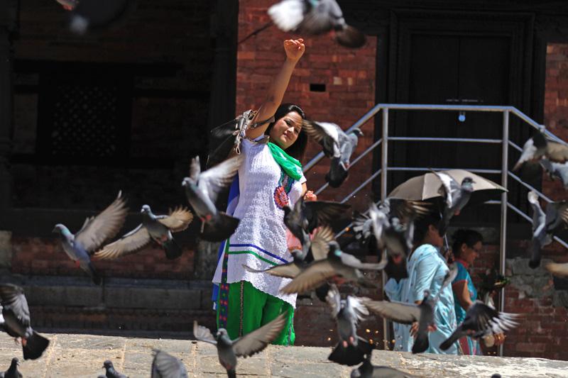 A woman feeding pigeons on the premises of Pashupathinath Temple, in Kathmandu. Photo: Skanda Gautam/ THT