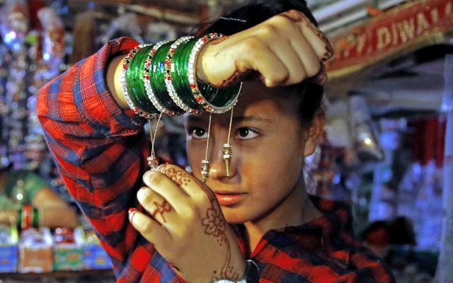 A woman trying on bangles for Shravan, a month when women worship Lord Shiva, at a store in Indra Chowk, Kathmandu, on Sunday. Photo: Skanda Gautam/ THT
