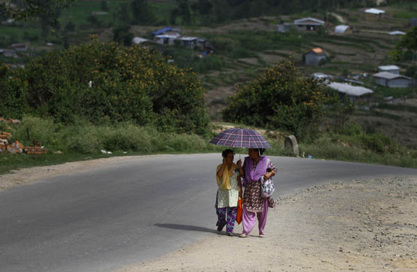 Women share an umbrella to shield themselves from sun as they walk up a road, in Chasikot, Lalitpur. Photo: THT