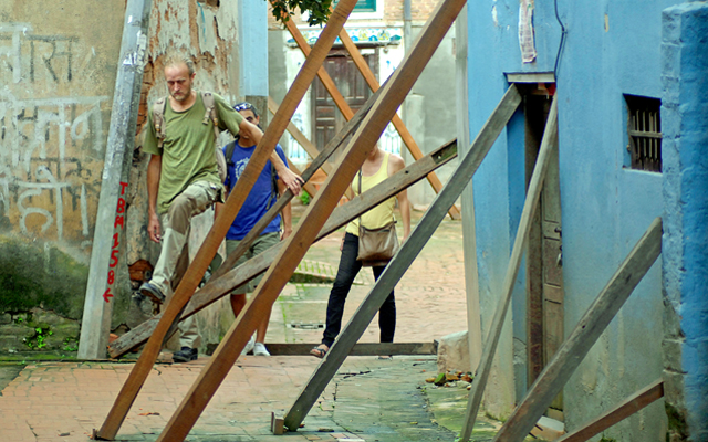 Tourists passing by wooden logs used to support damaged houses in Swatha, Lalitpur, on Sunday. Photo: THT