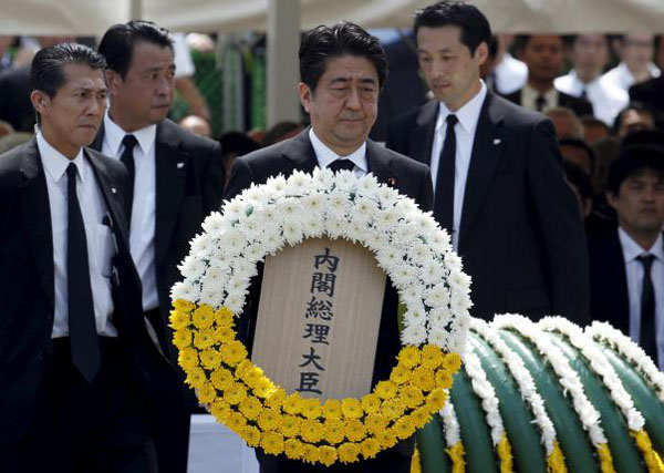 Japan's Prime Minister Shinzo Abe offers a flower wreath for the victims of the 1945 atomic bombing, during a ceremony commemorating the 70th anniversary of the bombing of the city at Nagasaki's Peace Park in western Japan, August 9, 2015. Photo:REUTERS