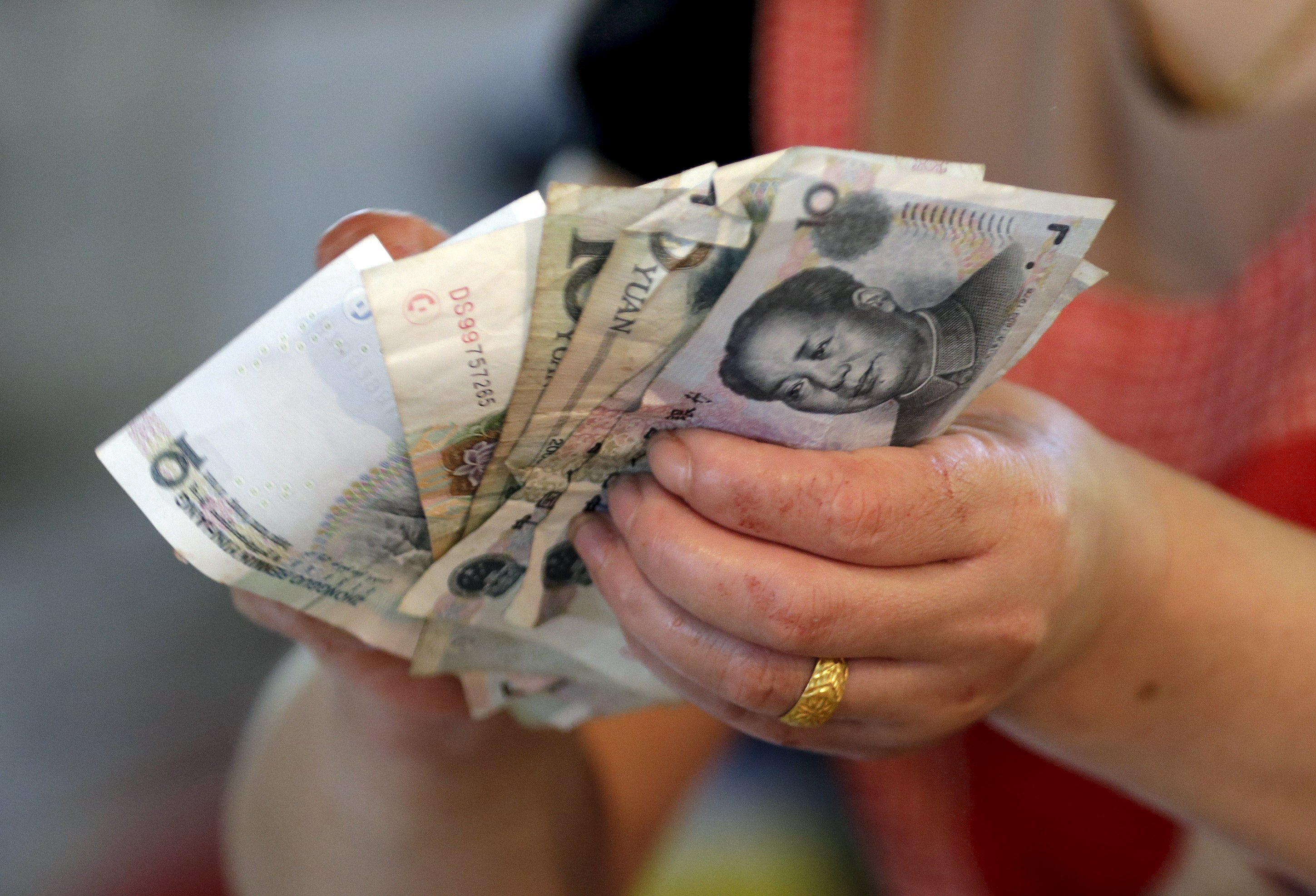 A vendor holds Chinese yuan notes at a market in Beijing in this August 12, 2015 file photo. China's yuan opened weaker against the dollar on August 17, 2015 but was stronger than the official midpoint fixed by the central bank.  Photo: Reuters