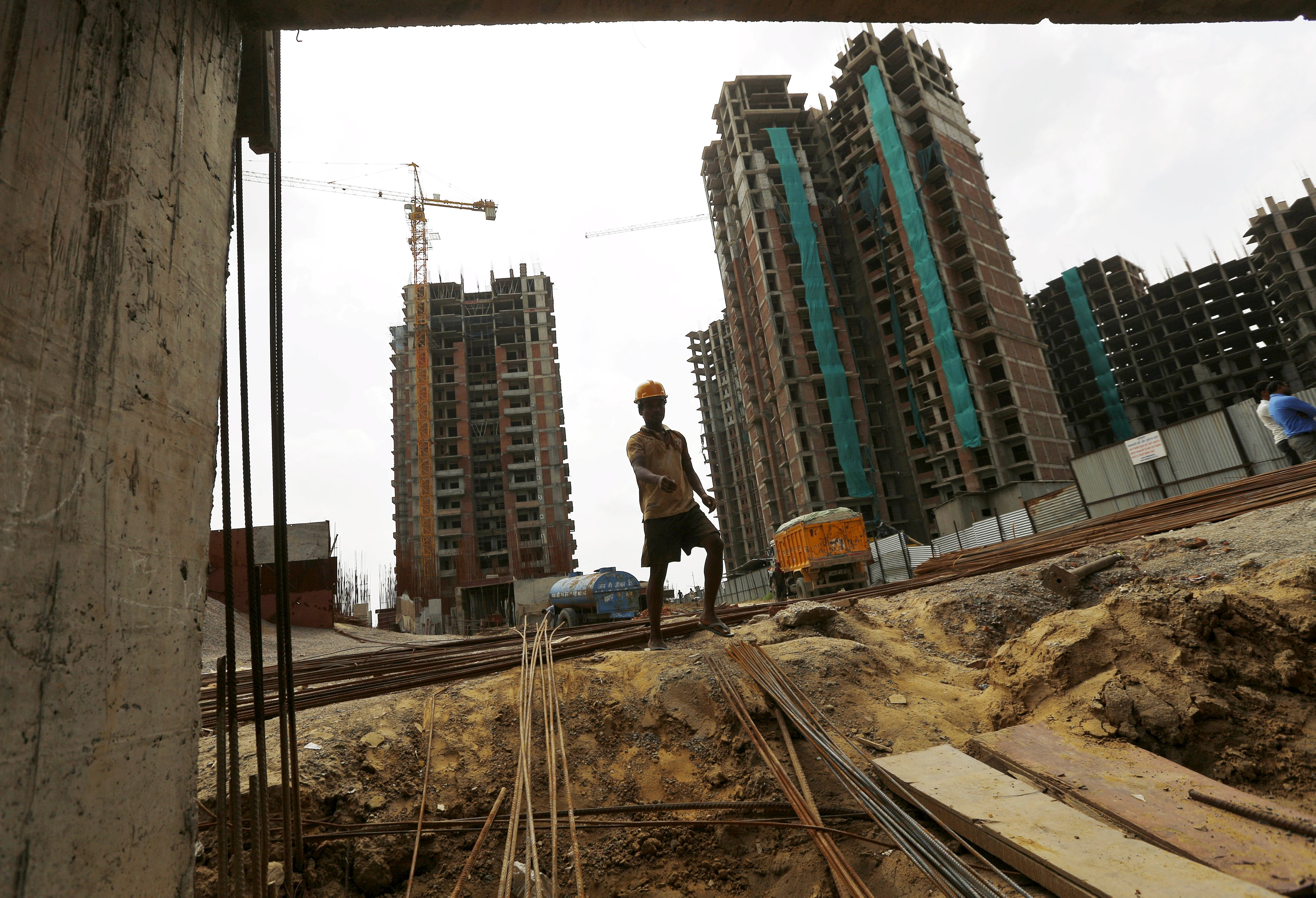 A labourer works at the construction site of a residential complex in Noida on the outskirts of New Delhi, India. Photo: Reuters