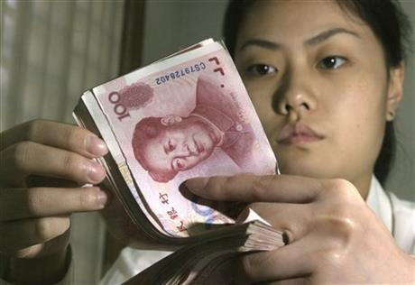 In this Aug. 7, 2003 file photo, a Chinese bank worker displays Chinese yuan at a bank in Beijing. China devalued its tightly controlled currency on Tuesday, Aug. 11, 2015, following a slump in trade, triggering the yuan's biggest one-day decline in a decade. The central bank said the yuan's 1.3 percent fall was due to a change aimed at making its exchange rate controls more market-oriented. But any change raises the risk of tensions with China's trading partners. Photo:AP
