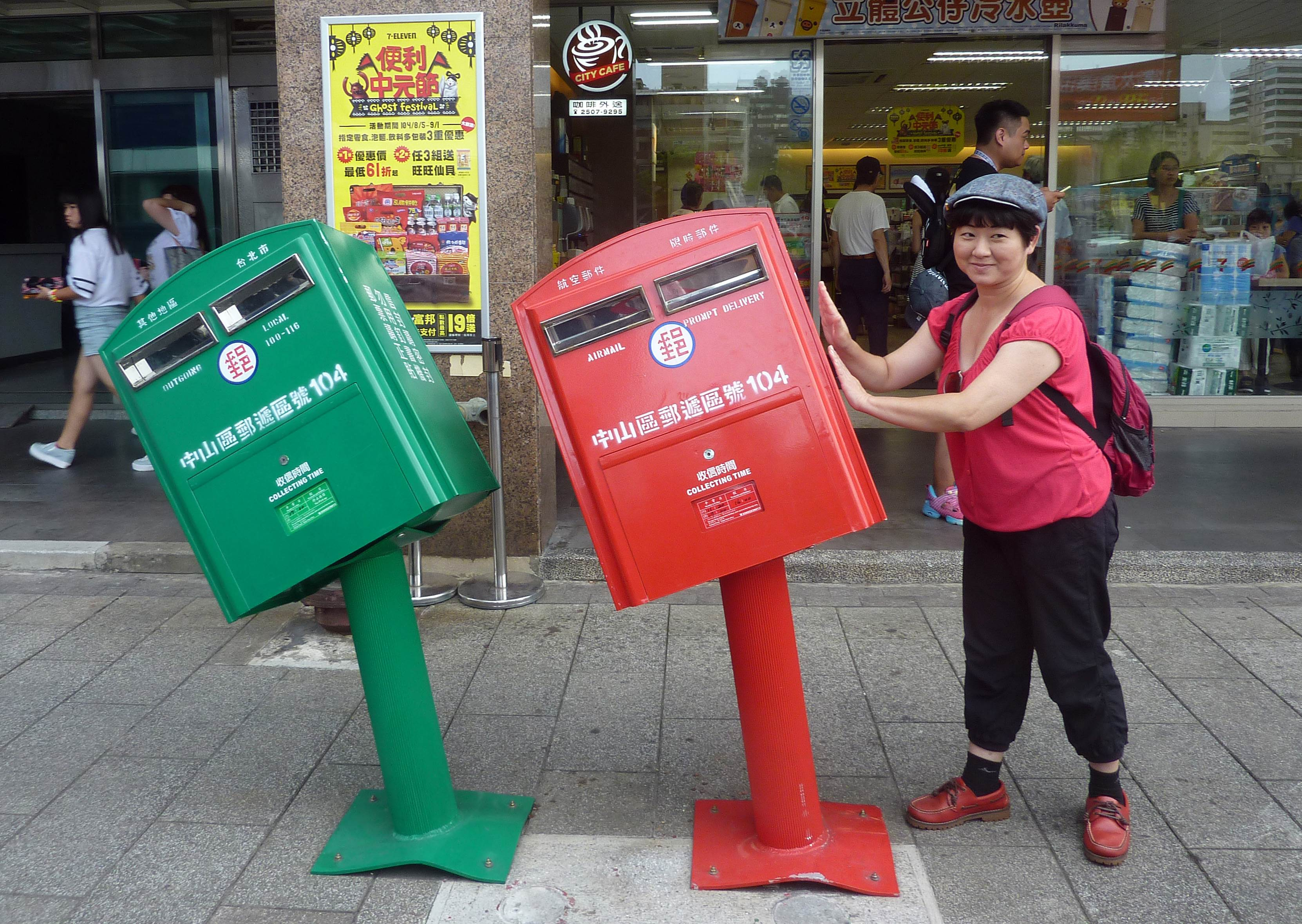 A woman poses next to two mailboxes along a street in Taipei on August 11, 2015 that were reportedly bent by strong winds brought by Typhoon Soudelor,which hit in the early hours of August 8 and was billed as the most powerful typhoon this year. The two iron mailboxes have become an unlikely attraction, drawing thousands of snap-happy visitors and have even become a backdrop to a wedding photo shoot. Photo: AFP