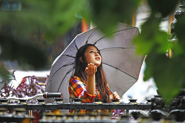 A girl feeling the raindrops fall on her hand while crossing a street in Jhochhen, Kathmandu, on Friday. Photo:THT
