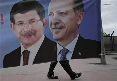 FILE - In this Thursday, May 28, 2015, file photo, a man walks past a poster with pictures of Turkish Prime Minister and leader of the AKP party Ahmet Davutoglu, left, and Turkey's President Recep Tayyip Erdogan and party's former leader, right, in Istanbul. In the wake of Turkey's June elections, President Recep Tayyip Erdogan appeared embattled, beaten and no longer in control of his political fate. Support for his ruling party has sunk, forcing it to seek a coalition alliance with opposition parties that were intent on reining him in. AP