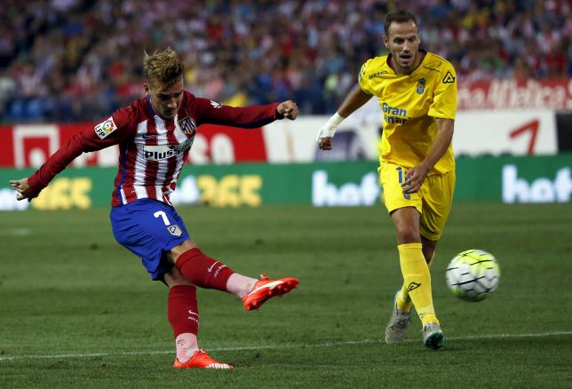 Atletico Madrid's Antoine Griezmann (L) kicks the ball past Las Palmas' Javier Castellano during their Spanish first division soccer match at Vicente Calderon stadium in Madrid, Spain,  August 22, 2015. REUTERS/Sergio Perez