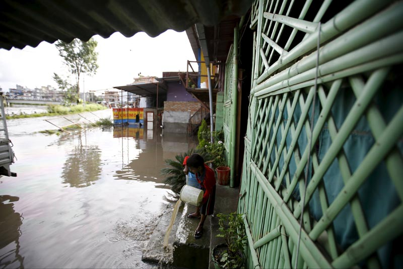 n    A boy uses a bucket to clear floodwaters from a house, which flowed in from the swollen Bagmati River caused by heavy rainfall, in Kathmandu, on August 17, 2015. Photo: Reuters