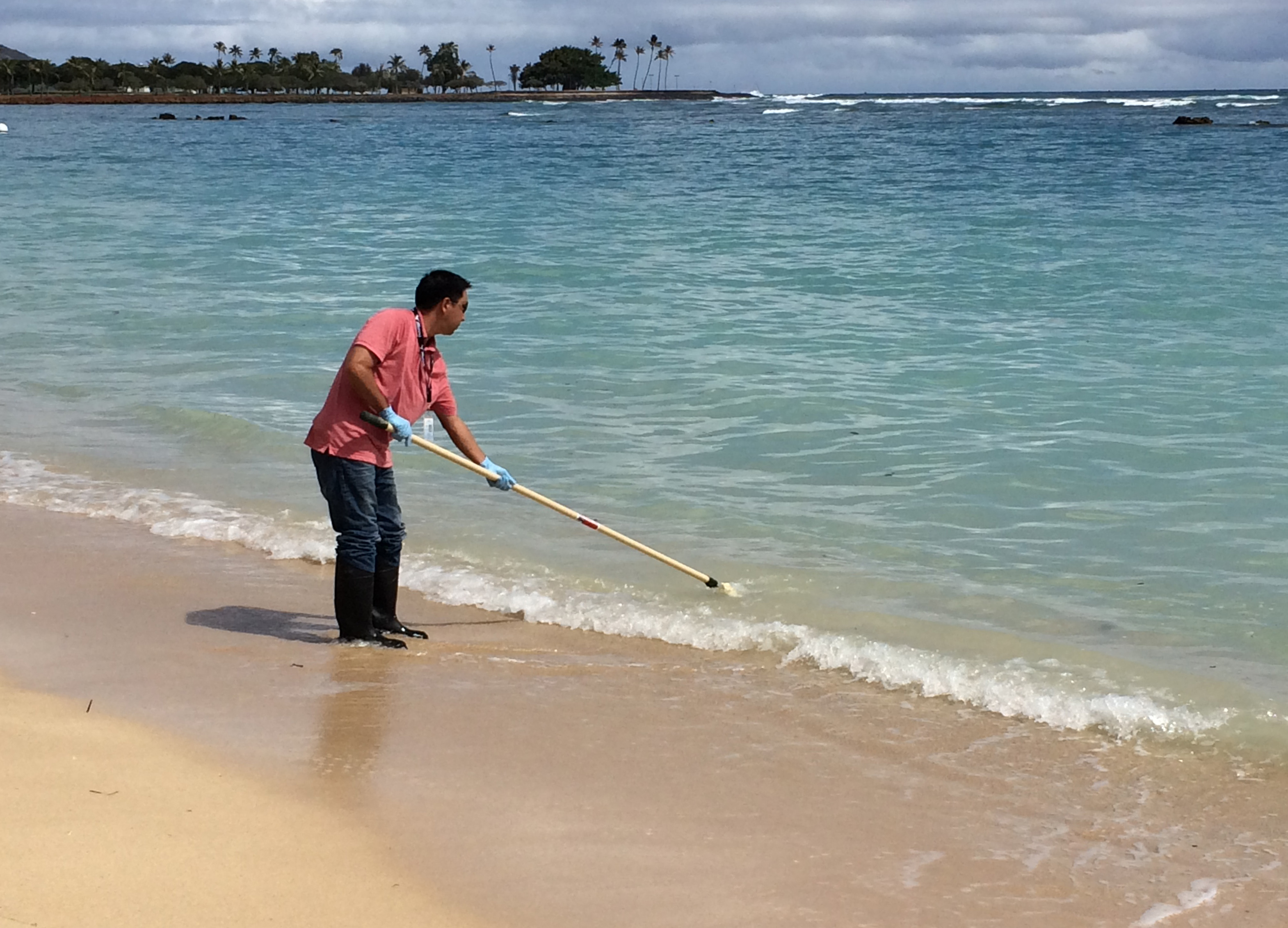 Scott Murakawa, of the Hawaii Department of Health, takes a water quality sample at Ala Moana Beach Park in Honolulu, Tuesday, August 25, 2015. Stretches of Waikiki's white sands and blue waters were deserted Tuesday after officials warned that heavy rains triggered a half-million-gallon sewage spill near Hawaii's world-famous tourist district. Photo: AP