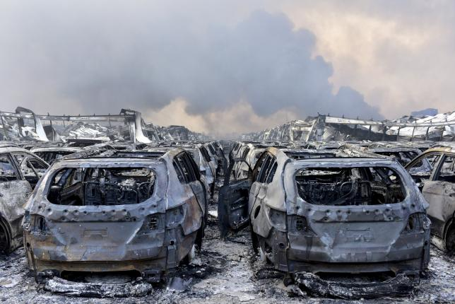 Damaged vehicles are seen as smoke rises from the debris after the explosions at the Binhai new district in Tianjin, China, August 13, 2015. REUTERS/Stringer