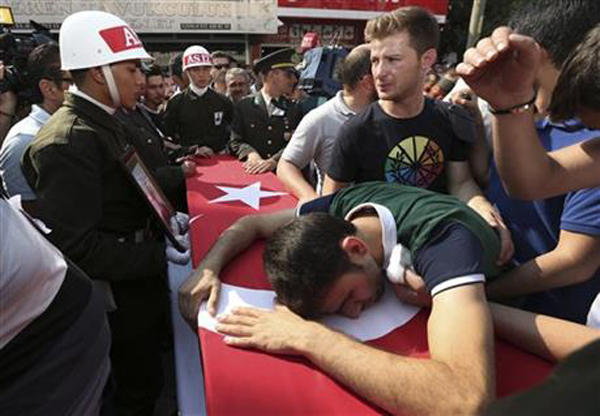 A relative cries over the Turkish flag-draped coffin of Turkish soldier Kagan Kandemir, during his funeral in the town of Civril, Turkey, Friday, July 31, 2015. Kandemir, was one of the three Turkish troops that were killed on July 30 when Kurdistan Workers' Party, or PKK militants opened fire on their convoy in the southeastern province of Sirnak, according to the army. Photo:AP