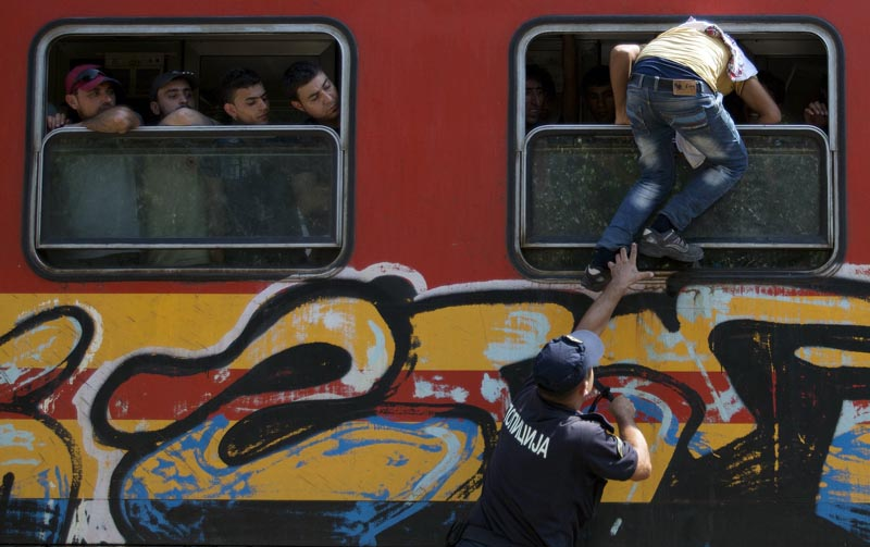 A policeman tries to stop a migrant from boarding a train through the window at Gevgelija train station in Macedonia, close to the border with Greece, August 15, 2015. In the past month, an estimated 30,000 refugees have passed through Macedonia, another step in their uncertain search for a better life in western Europe.  Photo: Reuters