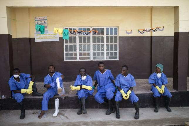 Ebola health workers rest outside a quarantine zone at a Red Cross facility in the town of Koidu, Kono district in Eastern Sierra Leone December 19, 2014.  nREUTERS/Baz Ratner