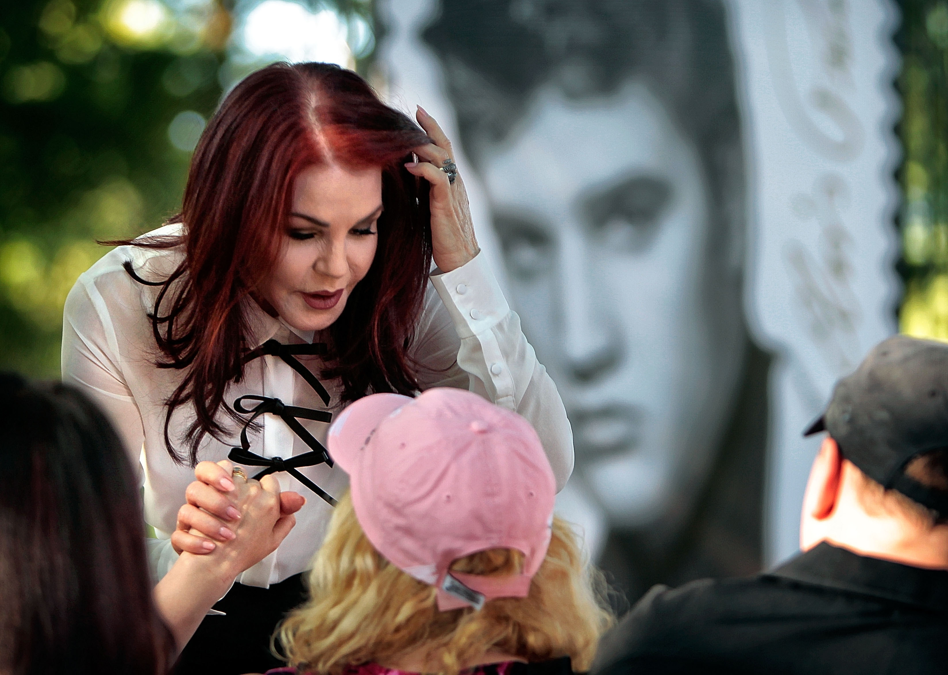Priscilla Presley greets enthusiastic Elvis fans and newlyweds Dawn and Phillip Pratt after a dedication ceremony for the new Elvis Forever stamp, the second postal stamp for the music icon, Wednesday, August 12, 2015, in Memphis. Mayor AC Wharton, Mayor Mark Luttrell, and  Megan Brennan, the USPS Postmaster General, spoke at the unveiling. Photo: The Commercial Appeal/ AP