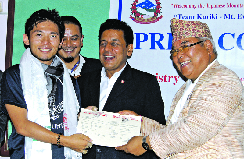 Kripasur Sherpa, Minister of Culture, Tourism and Civil Aviation handing over Everest climbing permit to Nobukazu Kuriki, leader of a Japanese expedition team at a programme, in Kathmandu, on Sunday. The team will be embarking on an expedition to Mt Everest by the end of August. Photo:THT
