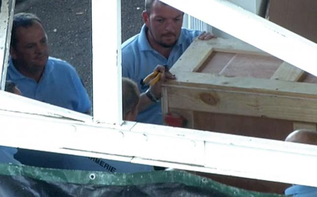 French gendarmes work on a oversized crate, believed to contain plane wreckage, in the cargo area of the airport in Saint-Denis on the French Indian Ocean island of La Reunion, in this still image taken from video shot on July 31, 2015. REUTERS/Reuters