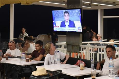 Greek Prime Minister Alexis Tsipras, on a screen during a televised address to the nation, as a tourist watches on a ferry traveling in the Aegean sea, near Syros island, Greece, Thursday, Aug. 20, 2015. AP
