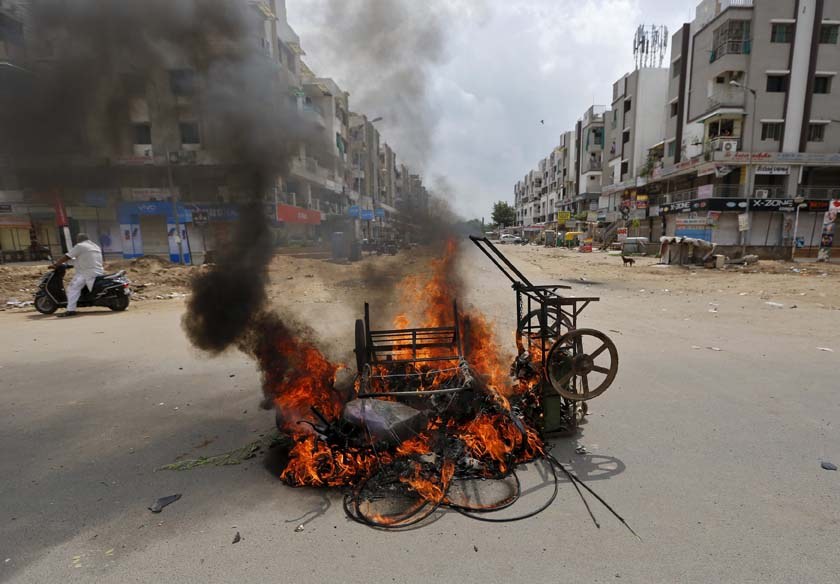 A man on a scooter stands next to burning vehicles after the clashes between the police and protesters in Ahmedabad, India, August 26, 2015. India deployed paramilitary forces and imposed a curfew in the western state of Gujarat on Wednesday after violence broke out at a protest led by a powerful clan to demand more government jobs and college places. Photo: Reuters