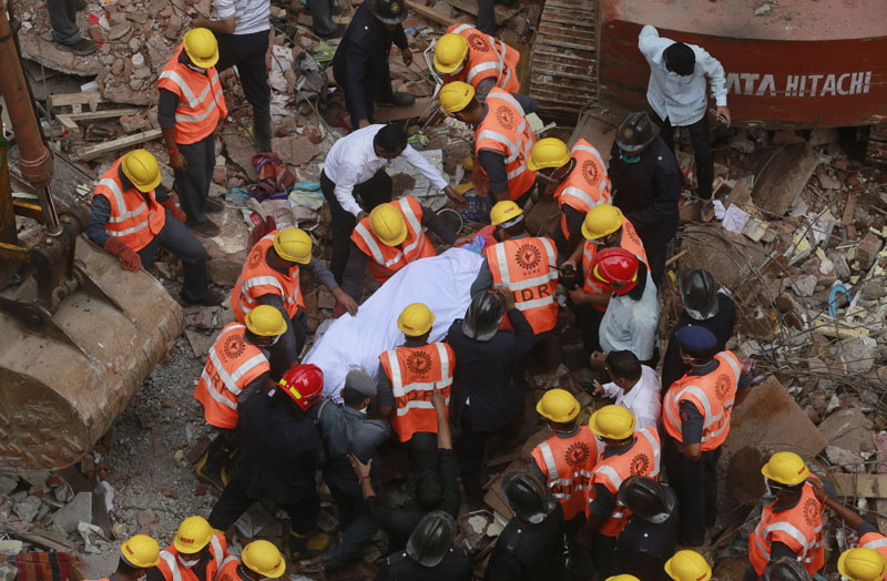 Rescue workers carry the body of a victim at the site of building collapse in Thane, outskirts of Mumbai, India, Tuesday, Aug. 4, 2015. Photo: AP