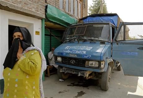 A Kashmiri woman walks near a police vehicle parked blocking the gate to the residence of senior separatist leader Syed Ali Geelani in Srinagar, Indian-controlled Kashmir, Thursday, Aug 20, 2015. AP