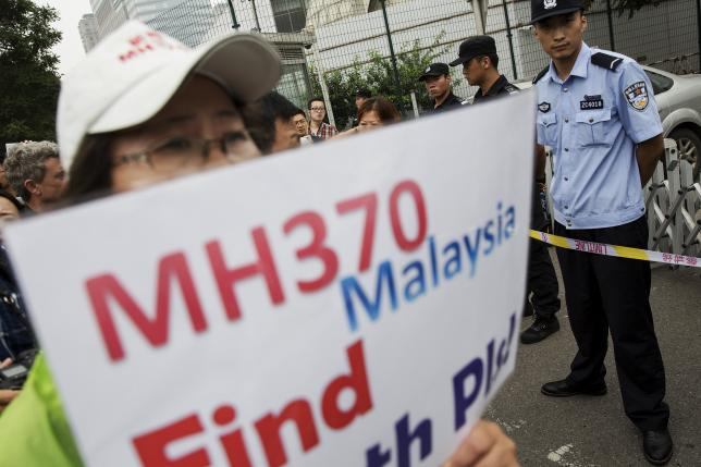 A woman whose relative was aboard Malaysia Airlines flight MH370 holds placard after police stopped protesting relatives from entering a road leading to the Malaysian embassy in Beijing August 7, 2015. REUTERS/Damir Sagolj